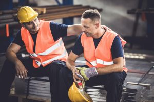 Construction worker supporting colleague
